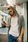 Jóvenes que utilizan smartphone en metro - foto de stock
