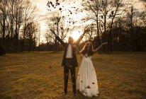 Щаслива подружня пара в парку радісно вітає і кидає листя. — стокове фото