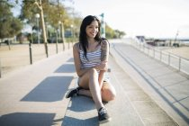 Sonriendo tatuado joven mujer relajándose en el banco - foto de stock