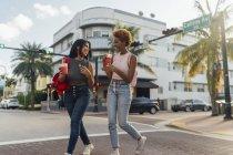 США, Флорида, Майамі-Біч, два щасливих подруг, що мають м'який напій і перетинаючи вулицю — стокове фото