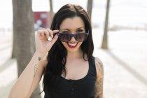 Ritratto di giovane donna scintillante con piercing al naso e occhiali da sole — Foto stock