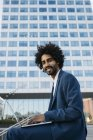 España, Barcelona, joven empresario sonriente sentado al aire libre en la ciudad y trabajando en el ordenador portátil - foto de stock