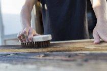 Handwerker mit Pinsel auf Holzstück — Stockfoto