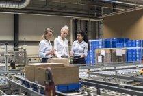 Три жінки обговорюють на конвеєрній стрічці на заводі — Stock Photo