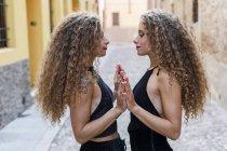 Vista laterale di gemelle in piedi faccia a faccia toccando le mani — Foto stock