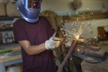 Craftswoman welding metal in her workshop — Stock Photo
