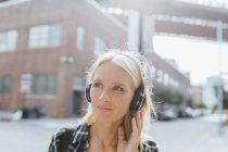 USA, New York, Brooklyn, ritratto di una giovane donna che ascolta musica con le cuffie in città — Foto stock