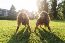 Сестры-близнецы отжимаются на лугу — стоковое фото