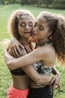 Portrait of twin sisters head to head hugging each other — Stock Photo