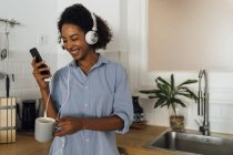 Woman with headphones, using smartphone and drinking coffee for breakfast in her kitchen — Stock Photo