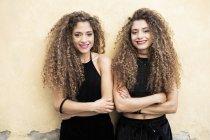 Портрет смеющихся сестер-близнецов, стоящих бок о бок — стоковое фото