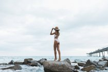 Rückansicht einer jungen Frau mit Badeanzug und Hut, die auf einem Felsen im Meer steht — Stockfoto