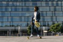 Espagne, Barcelone, jeune homme d'affaires à cheval skateboard dans la ville — Photo de stock