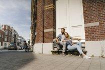 Paesi Bassi, Maastricht, giovane coppia che fa una pausa in città e si rilassa sulla panchina in strada — Foto stock