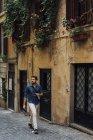 Homme d'affaires utilisant smartphone et écouteurs dans la rue — Photo de stock
