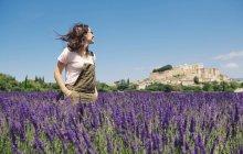 Francia, Grignan, donna sorridente in piedi nel campo di lavanda guardando il villaggio — Foto stock