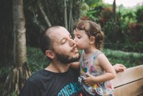 Baby girl kissing her father on cheek in a park — Stock Photo