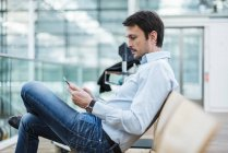 Homme d'affaires en attente dans la zone de départ de l'aéroport, en utilisant une tablette numérique — Photo de stock