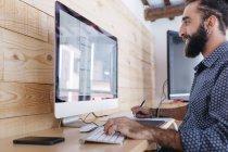 Lächelnder junger Mann, der zu Hause mit dem Computer am Grundriss arbeitet — Stockfoto