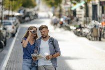Paesi Bassi, Maastricht, giovane coppia che esplora la città con la mappa e scatta foto sulla macchina fotografica — Foto stock