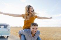 Jeunes couples espiègles au fourgon de campeur dans le paysage rural — Photo de stock