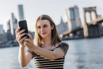 USA, New York, Brooklyn, portrait of young woman taking selfie with smartphone — Stock Photo