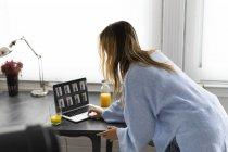Jeune femme regardant des photos sur ordinateur portable — Photo de stock