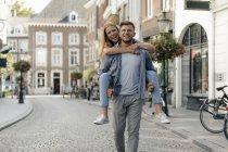 Нідерланди, Маастрихт, щаслива молода пара в місті, чоловік, що несе жінку на спині, piggyback — стокове фото