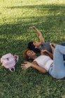 Duas amigas despreocupadas relaxando em um parque e ouvindo música — Fotografia de Stock