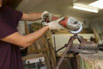Handwerkerin setzt Winkelschleifer in ihrer Werkstatt ein — Stockfoto