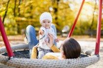 Retrato de bebê menina relaxante com sua mãe em um balanço no outono — Fotografia de Stock