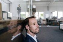 Homme d'affaires assis dans son bureau avec son portrait 3D derrière une vitre — Photo de stock