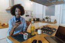 Woman having breakfast in her kitchen, using smartphone — Stock Photo