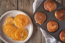 Candied orange slices on plate and tray with baked muffins — Stock Photo