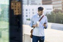 Homem maduro com café takeaway e fones de ouvido usando telefone celular na cidade — Fotografia de Stock
