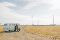 Camper van parked on dirt track in rural landscape with wind turbines — Stock Photo