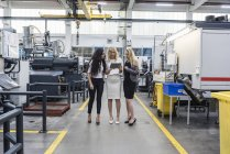 Three women with tablet talking in factory shop floor — Stock Photo