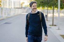 Sorridente uomo maturo con uno zaino in città in movimento — Foto stock