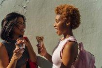 Два щасливих подруг з морозивом конуси говорити на стіні — стокове фото