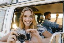 Retrato de mujer feliz con la cámara inclinada por la ventana de una furgoneta camper con el hombre conduciendo - foto de stock