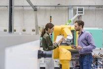 Geschäftsmann und Frau treffen sich vor Industrierobotern in einem High-Tech-Unternehmen — Stockfoto