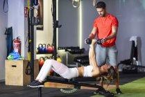 Personal Trainer unterstützt Klient beim Krafttraining, Hanteln heben, auf Bank liegen — Stockfoto