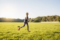 Mujer mayor corriendo en prado rural - foto de stock