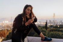 Spanien, barcelona, montjuic, junge frau sitzt in der dämmerung auf einer wand und benutzt handy — Stockfoto