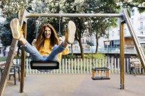 Spain, Barcelona, Red-haired girl having fun on swing — Stock Photo