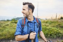 Smiling man hiking in the mountains and turning round — Stock Photo