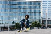 Spagna, Barcellona, giovane uomo d'affari accovacciato sullo skateboard in città — Foto stock