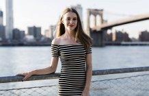 США, Нью-Йорк, Бруклин, портрет улыбающейся женщины в полосатом платье и стоящей перед Ист-Ривер — стоковое фото
