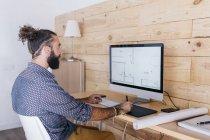 Junger Mann, der zu Hause am Grundriss arbeitet und den Computer benutzt — Stockfoto