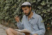 Молодой человек курит трубку, читает книгу — стоковое фото